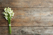 Leinwandbild Motiv Beautiful lily of the valley bouquet on wooden background, top view. Space for text