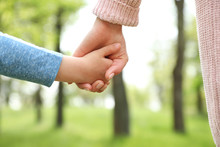 Little Child Holding Hands With His Mother Outdoors, Closeup. Family Time