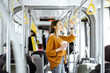 canvas print picture - Young woman passenger enjoying trip at the public transport, standing with coffee in the modern tram