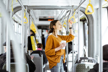 Young Woman Passenger Enjoying Trip At The Public Transport, Standing With Coffee In The Modern Tram