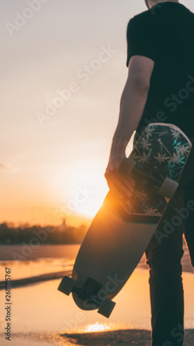 Fototapety, obrazy: The guy with the longboard at sunset.