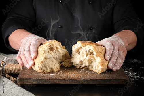 baker in black uniform broke in half a whole baked loaf of white wheat flour bread
