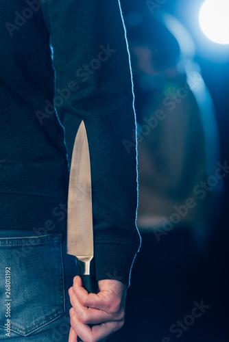 cropped view of murderer hiding knife behind back on black Wallpaper Mural