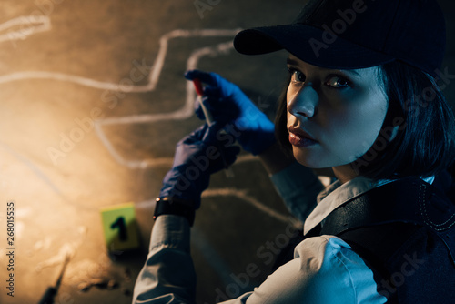Fototapeta investigator in rubber gloves looking at camera at crime scene