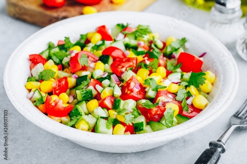 Obraz Fresh summer corn salad bowl with tomatoes, cucumbers, red onions and parsley. - fototapety do salonu