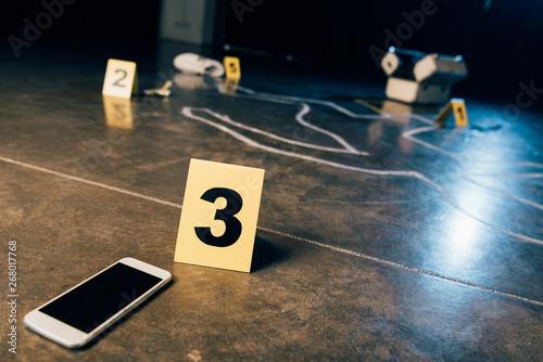Obraz na plátně chalk outline, smartphone with blank screen and evidence markers at crime scene