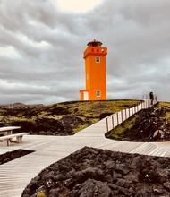 Orange Lighthouse Under Nimbus Clouds