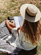 Woman In White Off-shoulder Dress Reading Book During Daytime