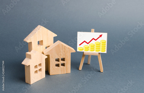 Wooden figures of houses and a poster with golden coins Canvas Print