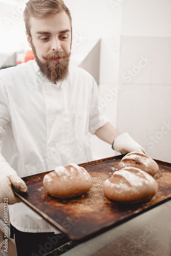 Keuken foto achterwand Bakkerij Charismatic baker holds the baking tray with newly-baked bread in the bakery