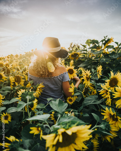 Foto op Aluminium Historisch mon. woman standing between blooming sunflowers during daytime