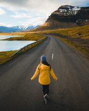 Woman Walking On Gray Paved Road