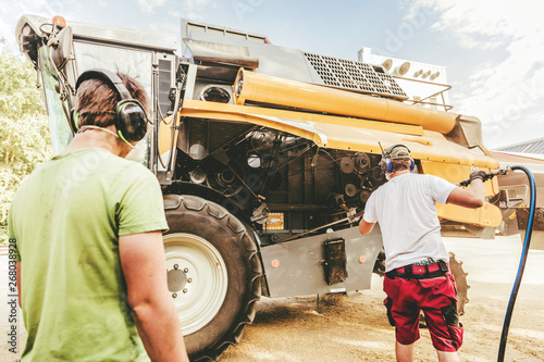 Fotografía  The mechanics repair the yellow and green combine harvester in the farm yard