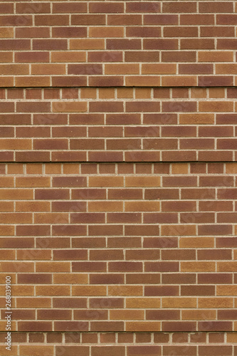 Reddish brown abstract brick wall background in common bond pattern with overlapping effect