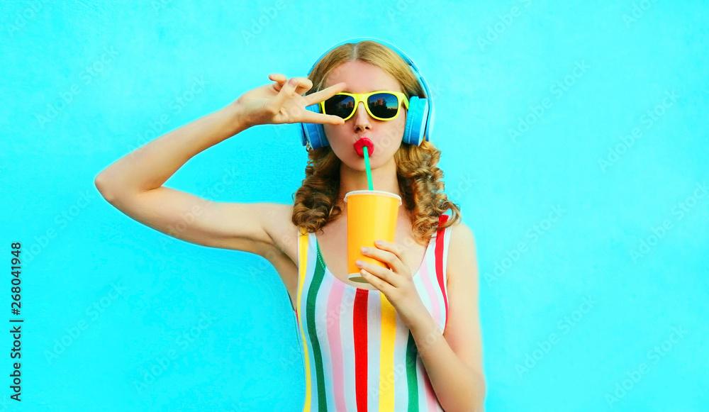 Fototapeta Portrait cool girl drinking fruit juice listening to music in wireless headphones on colorful blue background