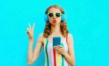 Portrait Cool Girl Blowing Red Lips Sending Sweet Air Kiss Holding Phone Listening To Music In Wireless Headphones On Colorful Blue Background