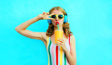 Portrait Cool Girl Drinking Fruit Juice Listening To Music In Wireless Headphones On Colorful Blue Background