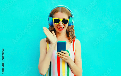 Photo sur Aluminium Magasin de musique Portrait surprised smiling woman holding phone listening to music in wireless headphones on colorful blue background