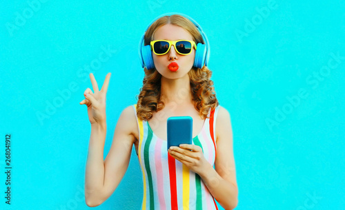 Poster de jardin Magasin de musique Portrait cool girl blowing red lips sending sweet air kiss holding phone listening to music in wireless headphones on colorful blue background