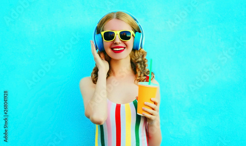 Photo sur Aluminium Magasin de musique Portrait happy smiling woman holding cup of juice listening to music in wireless headphones on colorful blue background