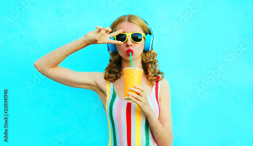 La pose en embrasure Magasin de musique Portrait cool girl drinking fruit juice listening to music in wireless headphones on colorful blue background