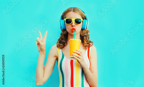 Poster de jardin Magasin de musique Portrait cool girl drinking fruit juice listening to music in wireless headphones on colorful blue background