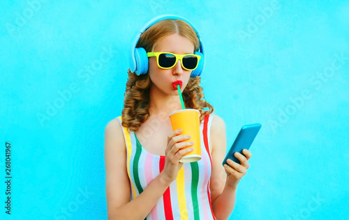 Portrait cool girl drinking fruit juice holding phone listening to music in wireless headphones on colorful blue background - 268041967