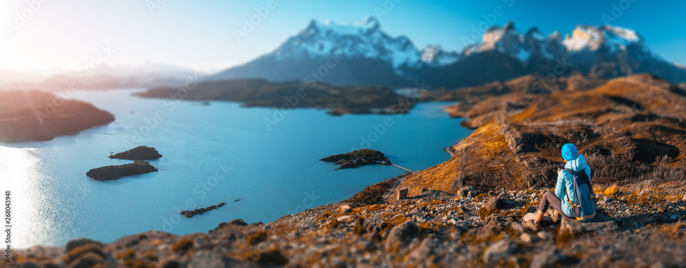 Fototapety, obrazy: Woman hiker sits on the rock and enjoys spectacular view of the snow capped mountains and the blue lake in the Torres del Paine National Park in Chile. Tilt shift effect applied