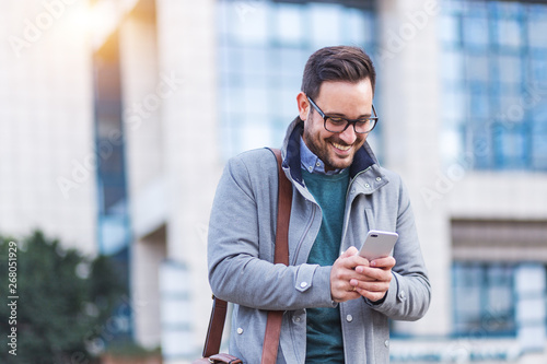 Fotografiet  Handsome businessman using smartphone with smile on the face
