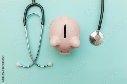 Leinwand Poster Medicine doctor equipment stethoscope or phonendoscope and piggy bank isolated on trendy pastel blue background