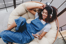 Blissful Black Young Woman In Vintage Denim Clothes Chilling On Terrace In White Headphones. Attractive Girl Enjoying Fresh Air On Balcony And Listening Music In Earphones In Morning.