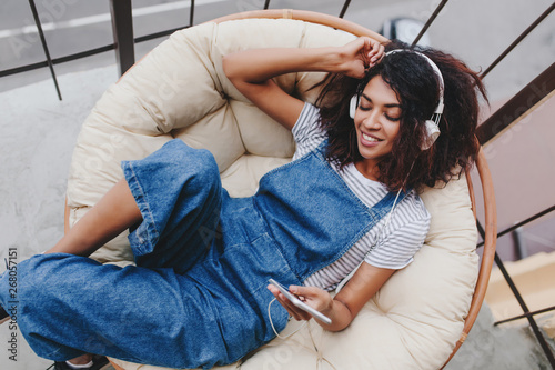 Fotografía Blissful black young woman in vintage denim clothes chilling on terrace in white headphones