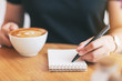 Closeup image of a woman writing on blank notebook while drinking coffee