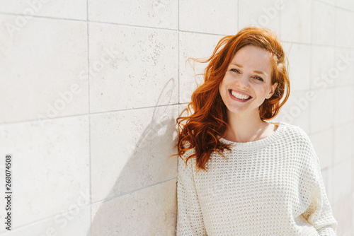 fototapeta na ścianę Smiling young woman near white wall