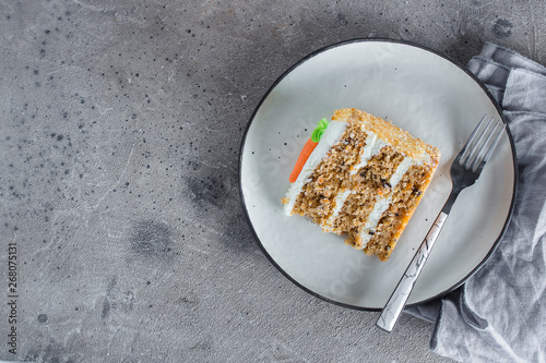 Fotografija Slice of homemade carrot cake with cream cheese frosting on plate on gray stone