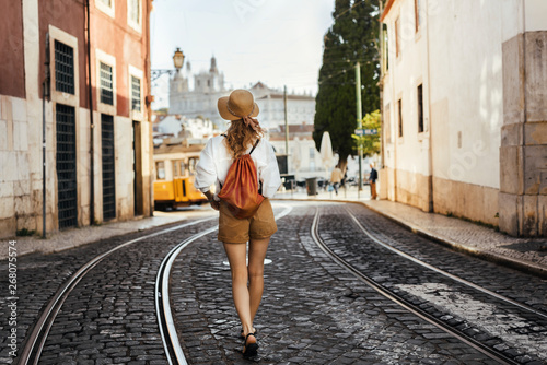Young woman walking on the street of european southern city wearing safari shorts, white shirt, hat and golden bag with yellow Lisbon tram and Alfama in the background