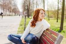 Casual Relaxed Young Woman Sitting On A Park Bench