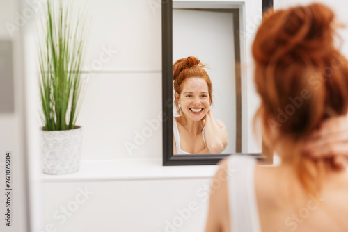 Happy young woman grinning at her reflection
