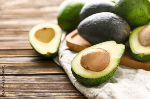 Photo  Board with fresh avocado on wooden background