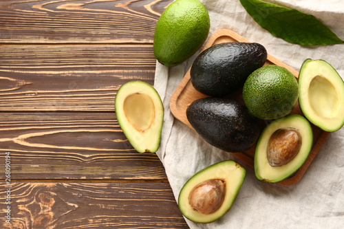 Fotografía Board with fresh avocado on wooden background