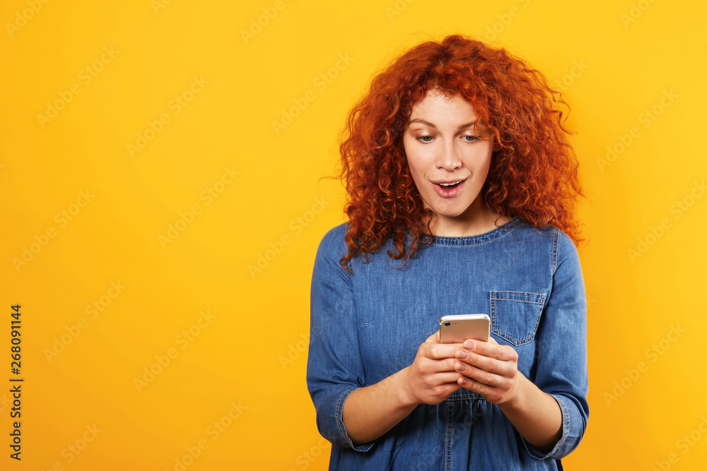 Fototapety, obrazy: Surprised redhead woman with mobile phone on color background
