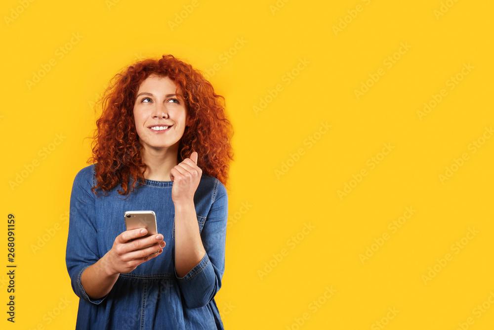 Fototapeta Thoughtful redhead woman with mobile phone on color background - obraz na płótnie