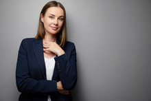 Confident Young Business Woman In Suit Looking At Camera. Grey Background With Copy Space.