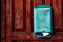 A Turquoise Vintage Mailbox Hangs On The Weather-shattered Door With Shabby Red Paint