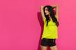 Leinwandbild Motiv Beautiful Young Brunette Is Posing Against Pink Sunny Background