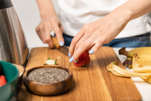 Cropped View Of Woman Cutting Organic Strawberry On Chopping Board Near Bananas On White
