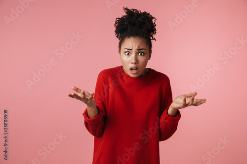 Fotografía  Beautiful young confused african woman posing isolated over pink wall background