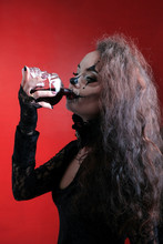 A Halloween-style Brunette In Black Clothes Drinks Red Liquid That Looks Like Blood From A Skull Decanter. Horrible Girl With A Scary Mouth And Eyes, Body Art. The Image Of A Witch Or An Evil Clown.