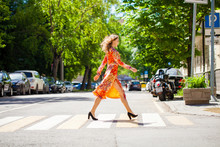 Young Beautiful Blonde Woman In A Red Flower Dress Crosses The Road At A Crosswalk