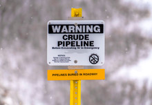 Close Up Of A Warning Sign On An Area With Crude Pipeline Viewed In Winter